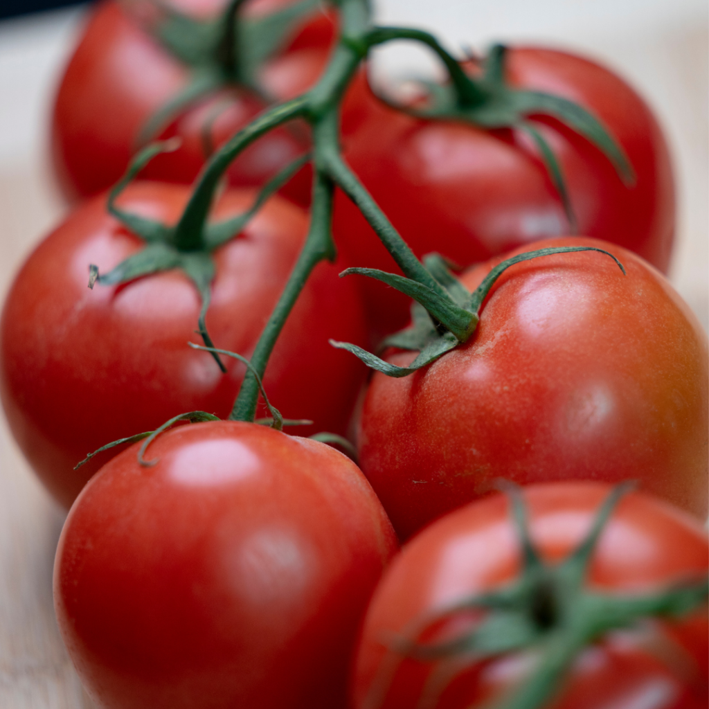 Photo of ripe tomatoes connected to a vine but sitting on a cutting board